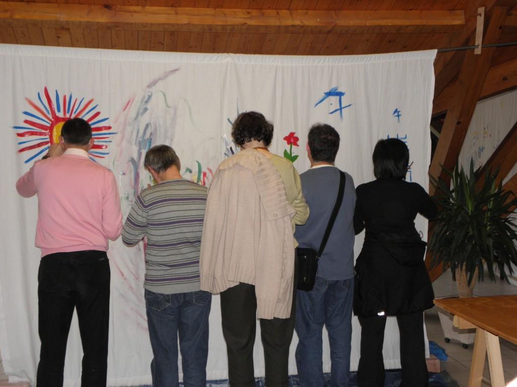 Pause Arc en ciel des 10èmes Journées Voix : 5 personnages de dos dessinent sur un même grand drap